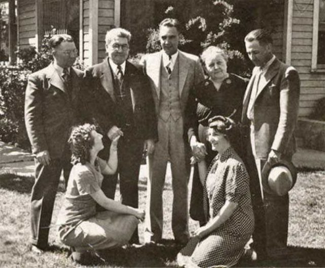 The Mad Seelys at Home (about 1935). We find Leola and Verna front and center in this exceedingly precious photo of the Five Mad Seelys and their parents, dating from the late 1930s or very early 1940s (Grandma died in 1943; Grandpa, in 1945). Behind the sisters stand Jim (F Leland), A. M., Grant, Alfaretta, and Elwyn. The scene, by the way, is the front yard of the Seely homestead in Brigham City. Over Uncle Grant's head, almost obscured by his distinctive altitude, you can just make out the front door. If the porch swing is still there, it's out of sight. (Description by Richard Anderson)