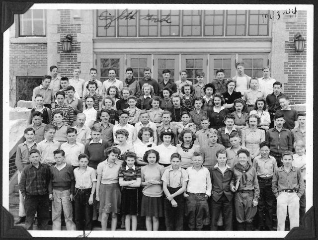 Lynn Richman, 8th grade school photo, 1943-44, 1st pose. Lynn is front row 3rd from left with chain on belt. Glen Seely is front row 4th from right in scout uniform.