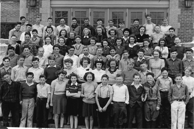 Lynn Richman, 8th grade school photo, 1943-44, 2nd pose. Lynn is front row 3rd from left with chain on belt. Glen Seely is front row 4th from right in scout uniform.