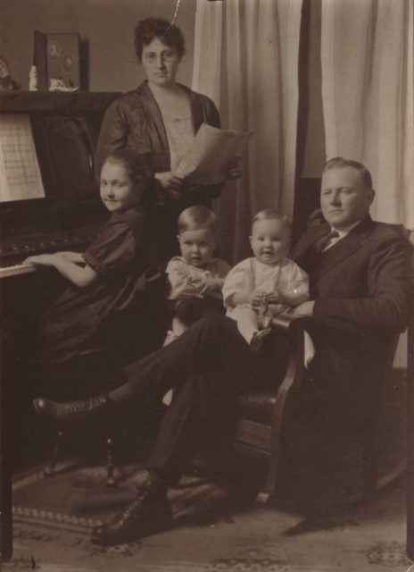Grace Elizabeth Pfeiffer is pictured here playing the piano. Also in the picture (from left to right): Grace's mother Elizabeth Combs (1887-1974), her brother Howard George Pfeiffer, her brother William Harold Pfeiffer (baby on lap), and her father George Washington Pfeiffer (1884-1944).