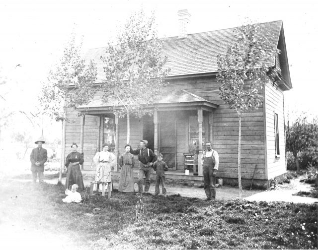 Home of John William Richman and Jane Charlotte Sinfield in Paradise, Utah. Left to right: John William Richman, lady, baby, lady, Estella Thomas (Boston Obray Thomas' sister), George Richman (Leon Sinfield Richman's brother), boy, man.